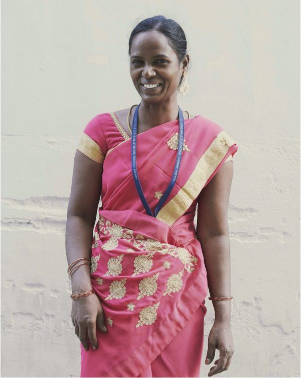 An smiling Indian woman is facing the camera.