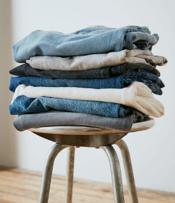 Une pile de jeans sur une chaise.