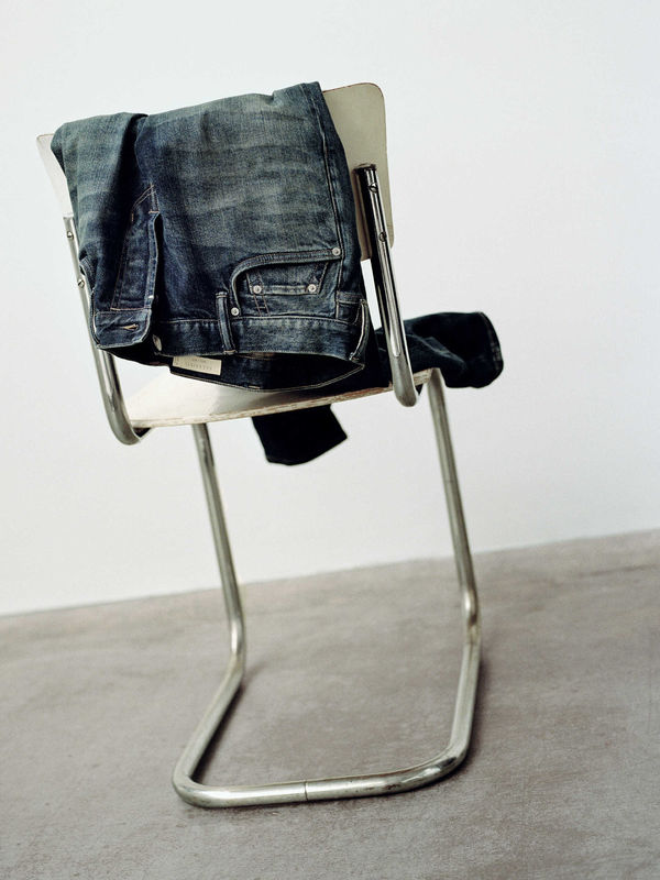 A pair of dark indigo jeans thrown at the back of a chair.
