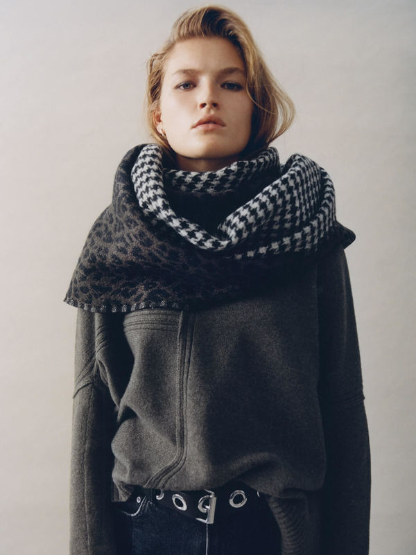 Woman standing wearing a dark grey jumper with an obersize printed scarf around her neck.