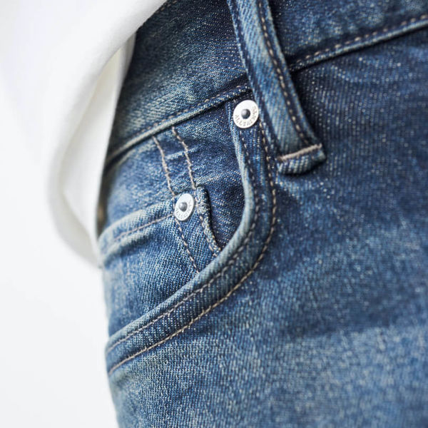 Close up on the watch pockets of a pair of jeans on a model.
