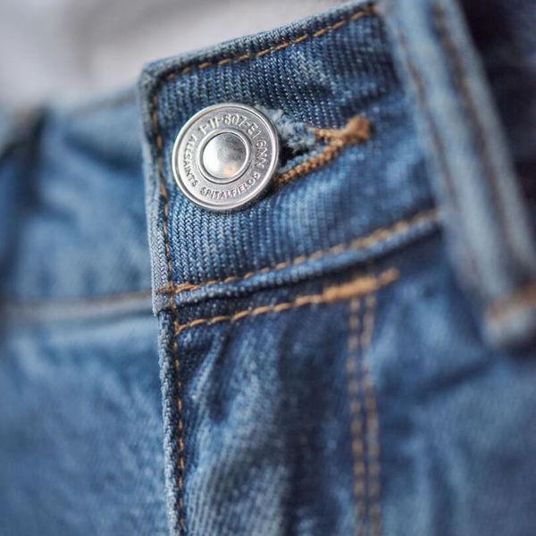 Gros plan sur le bouton de l'un de nos jeans.