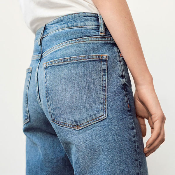 Close up on the back pockets of a pair of jeans on a model.