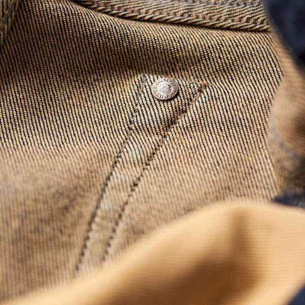 Close up on the stitching and rivet hidden on the inside of the jeans.