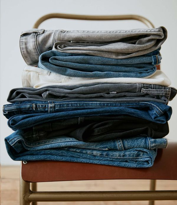 Pile of jeans on a chair.