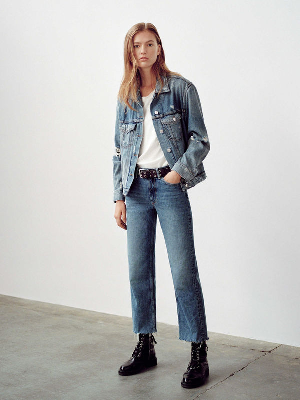Woman wearing a denim jacket with a white t-shirt, denim jeans and  black leather boots.