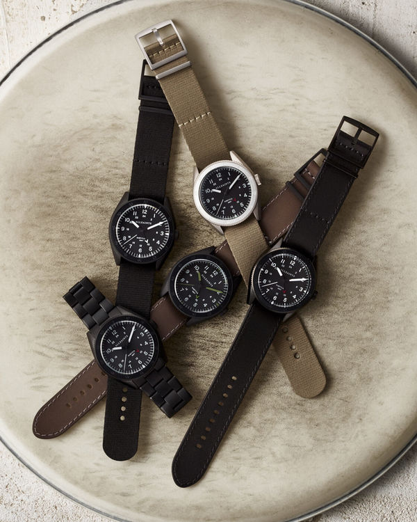 Image of the watches from the Subtitled GMT collection set on top of a drum set.