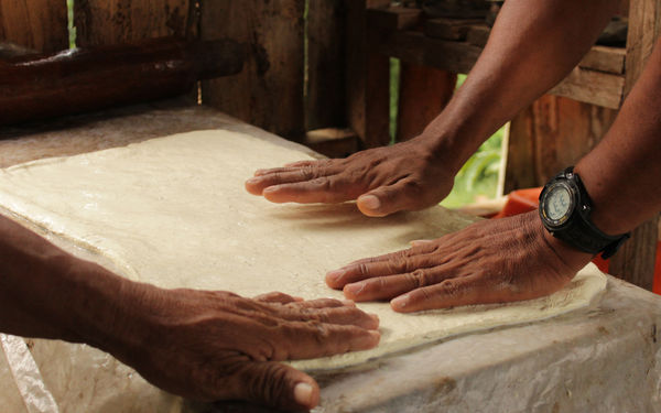 Image of hands flattening rubber on a table