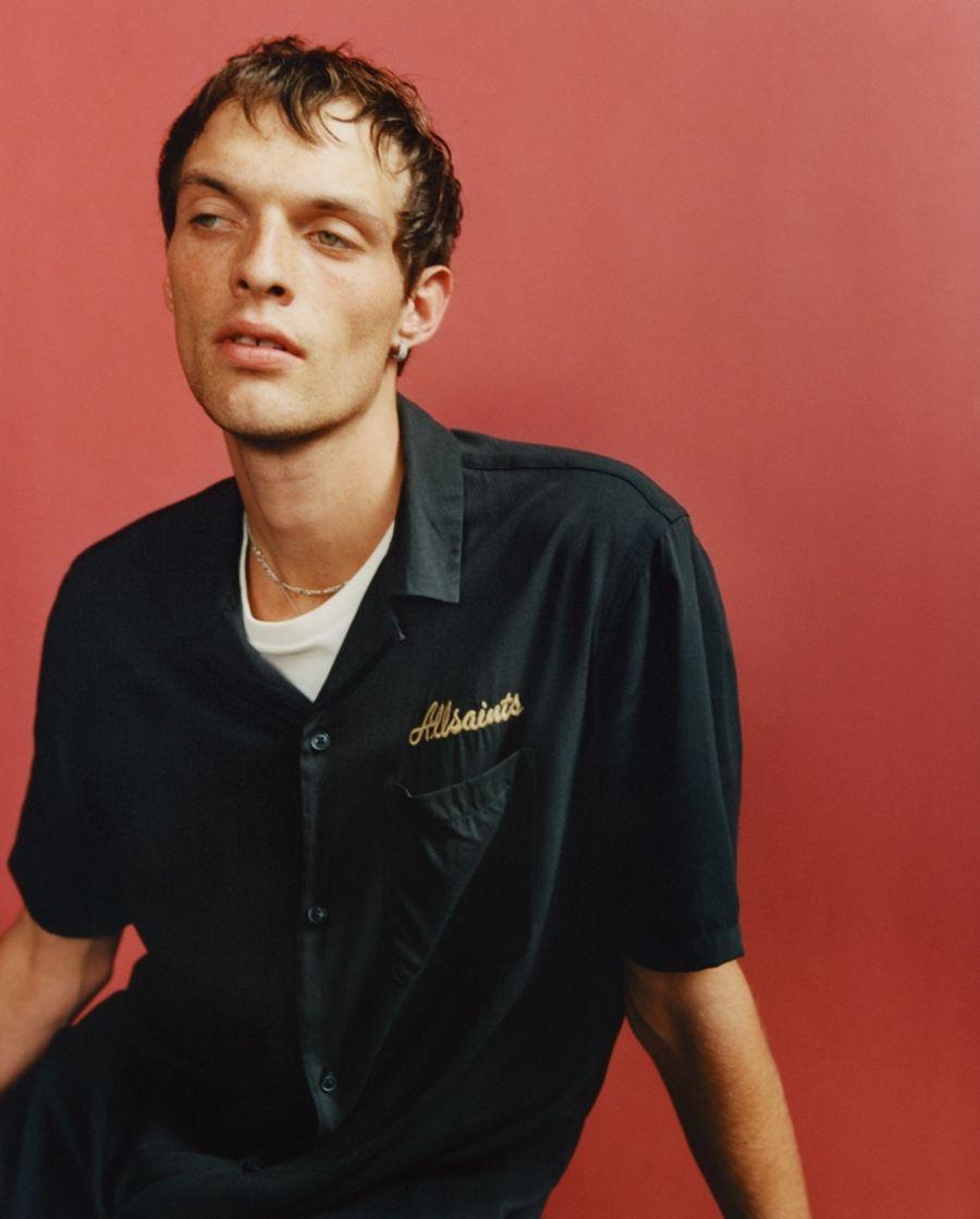Portrait d'un homme portant une chemise noire à manches courtes avec une broderie AllSaints sur la poche gauche.