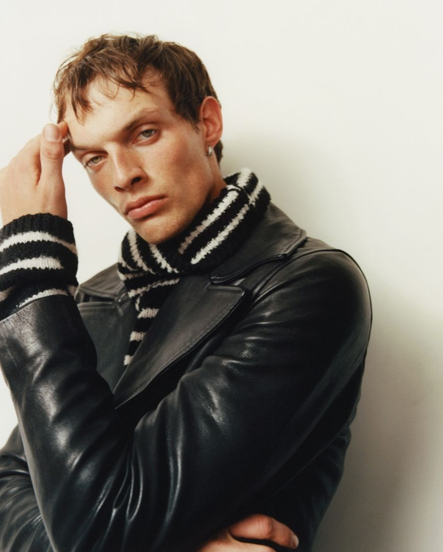 Portrait of a man wearing a black leather jacket over a black and white striped roll neck jumper.