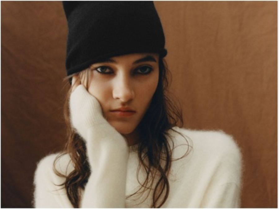 Portrait of a woman wearing a white jumper with a black beanie..