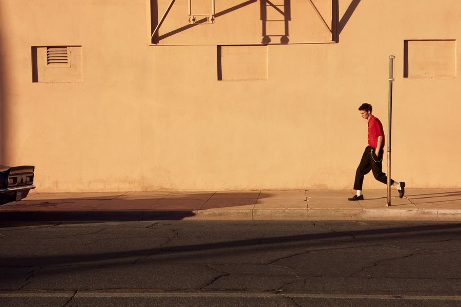 Image of a man walking in the street wearing black tailored pants with a red short sleeve shirt.