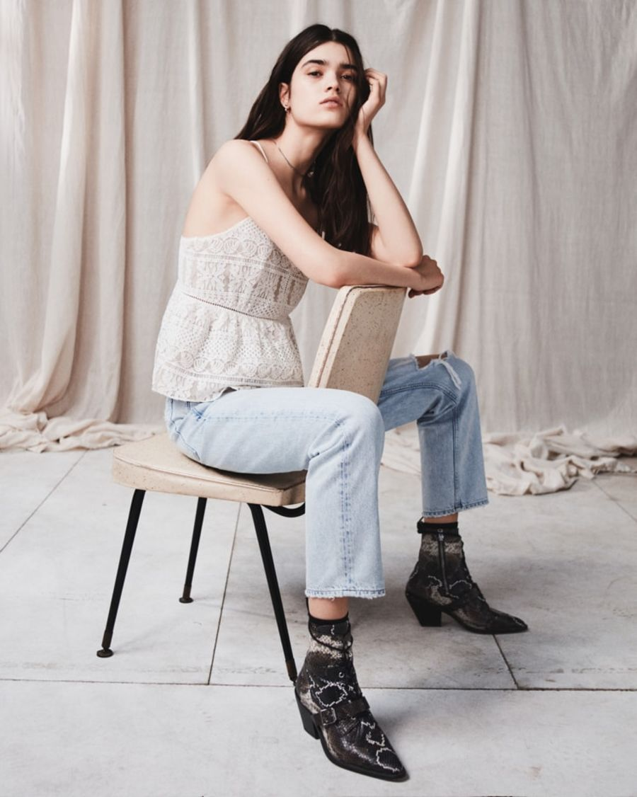 Image of a woman sitting on a chair wearing a thin straps lace top with lice denim jeans and snake printed boots.