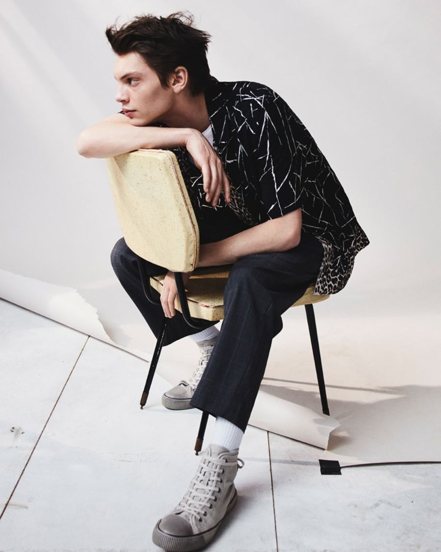 Image of a man sitting on a chair wearing a printed shirt with a white t-shirt, dark checked tailored trousers and grey trainers.