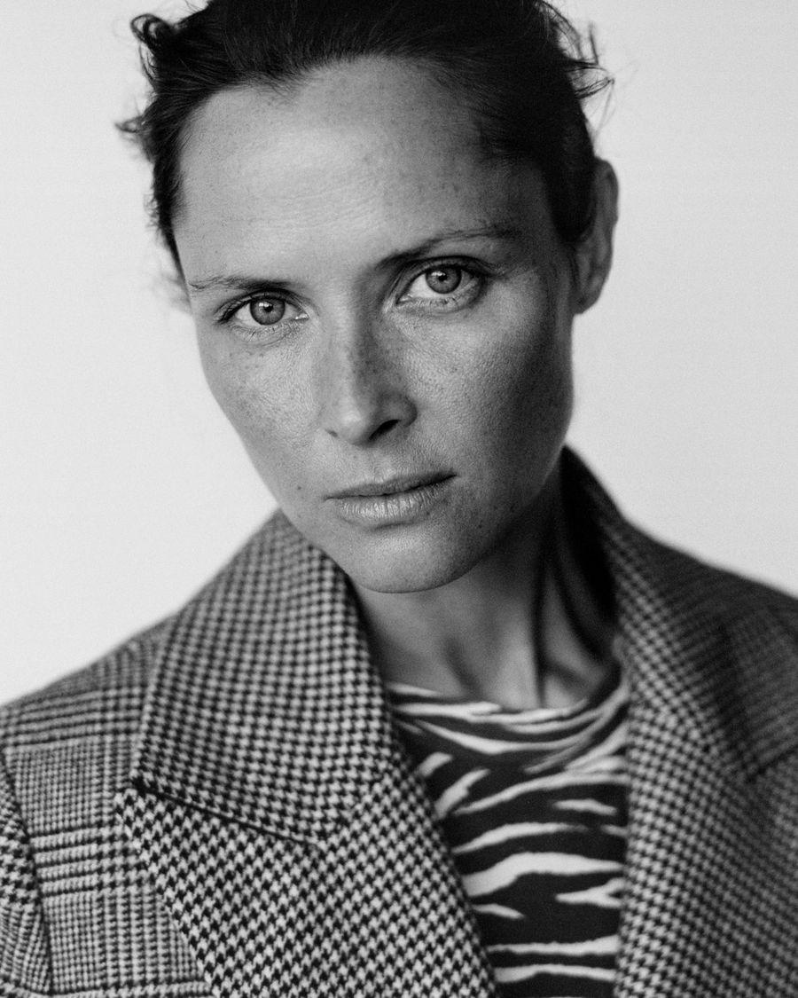 Black and white portrait of a woman wearing a checked coat over a zebra print t-shirt.