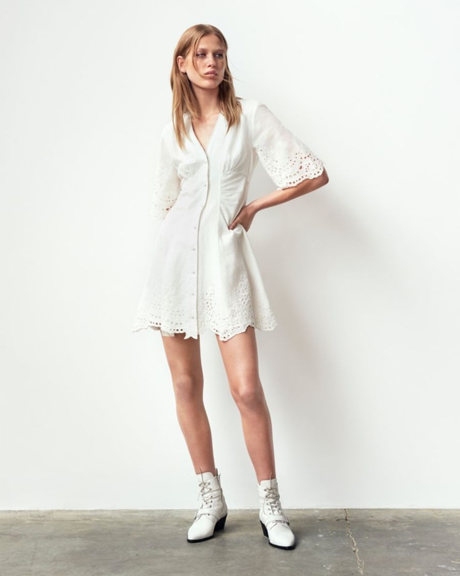 Image of a woman wearing a short white dress with white lace up boots.