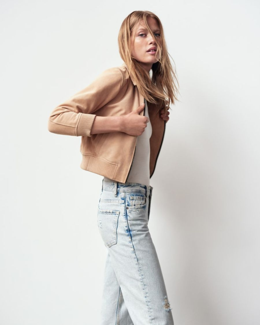 Portrait of a woman wearing a light pink suede biker jacket with a white t-shirt and light blue denim shorts.