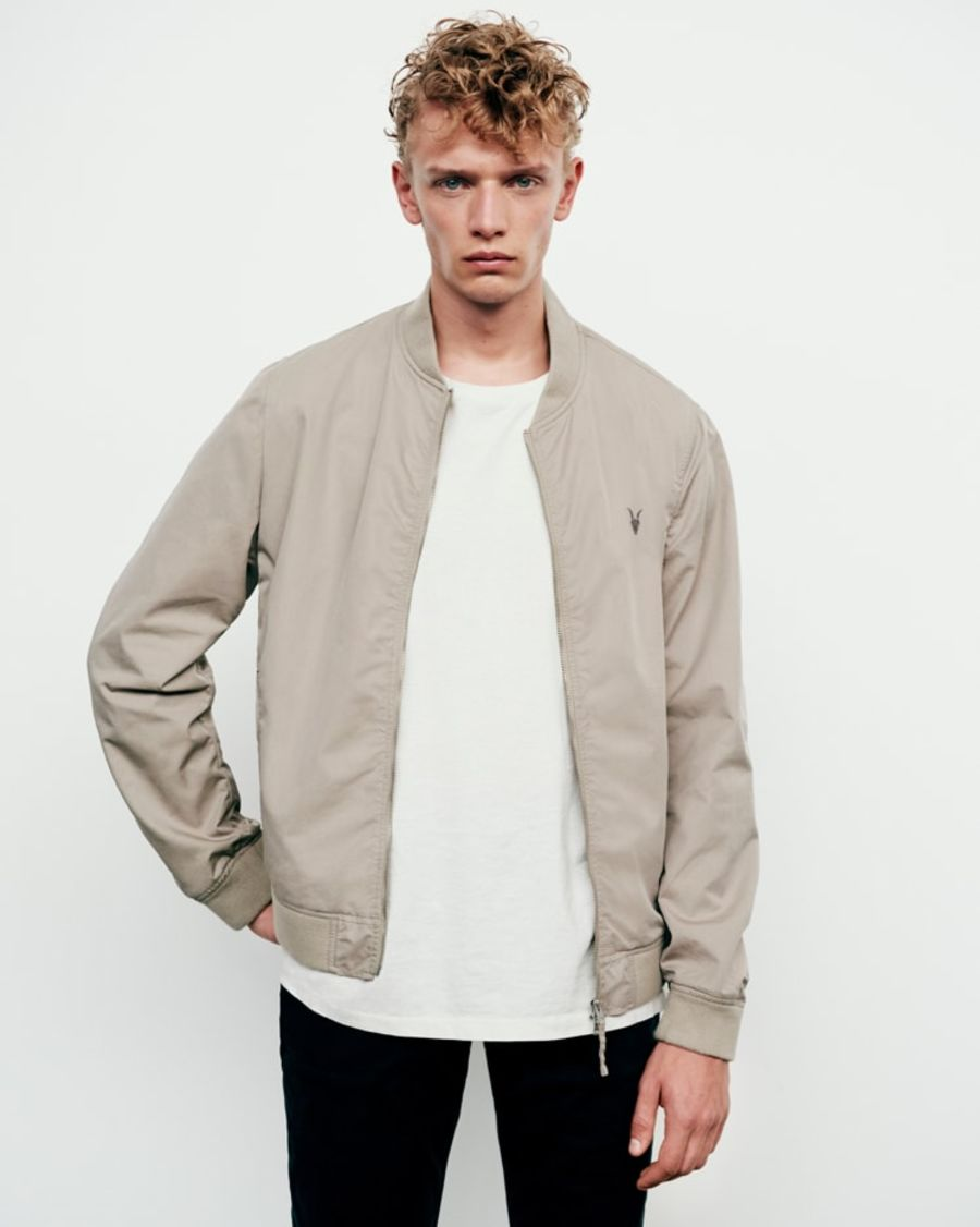 Portrait of a man wearing a cement coloured Ramskull bomber jacket with a white T-Shirt and black jeans.