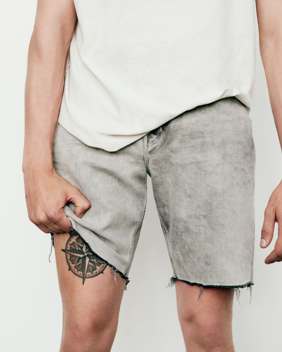 Close up on the legs of a man wearing light grey cut-off denim shorts.