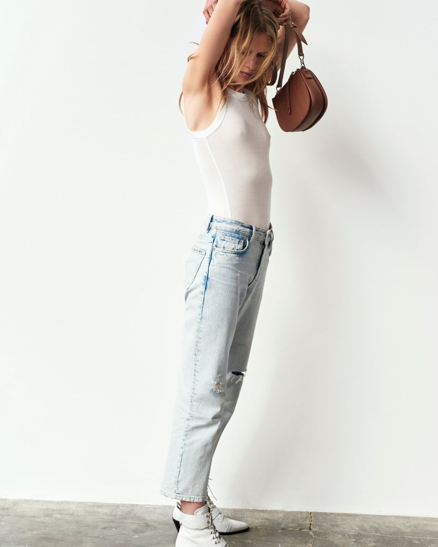 Image of a woman wearing a white tank top with light denim jeans, white boots and holiding a light brown handbag above her head.
