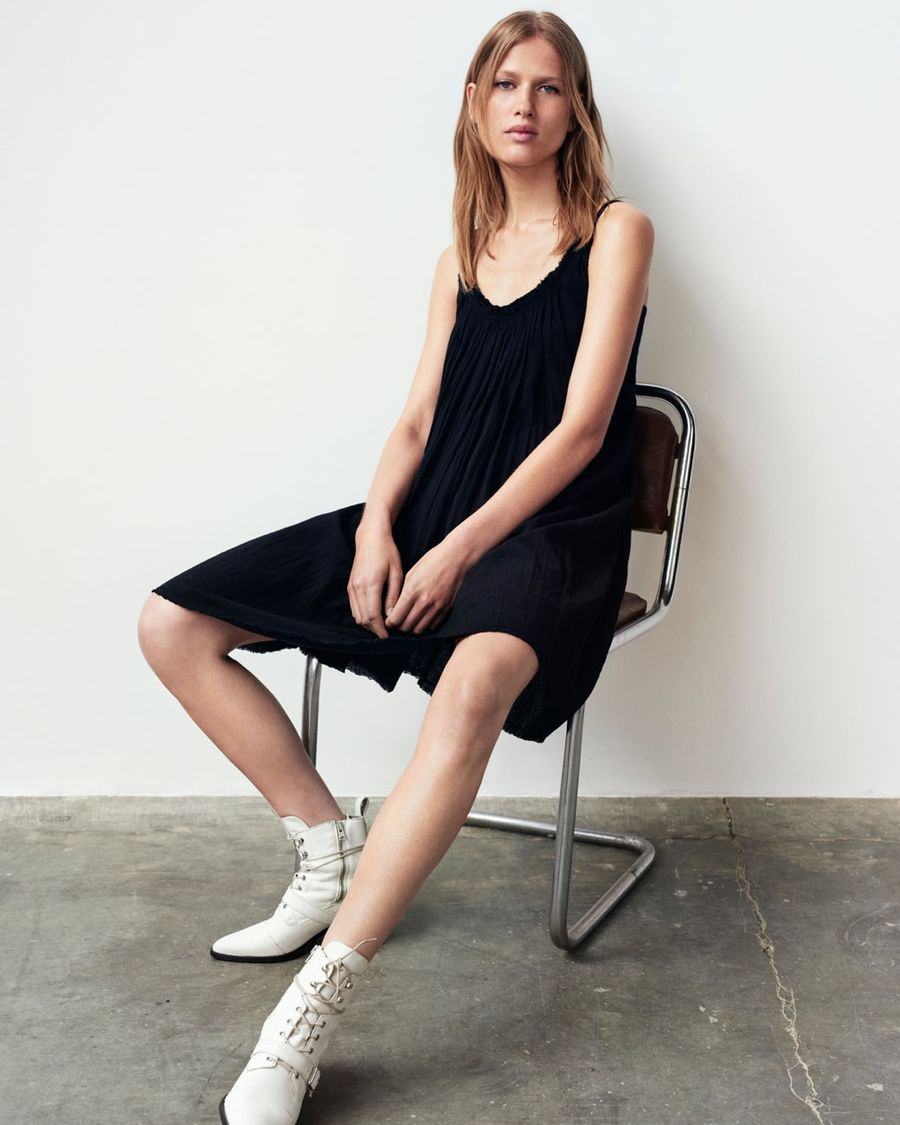 Image of a woman sitting on a chair and wearing a black oversized short dress with white lace up boots.