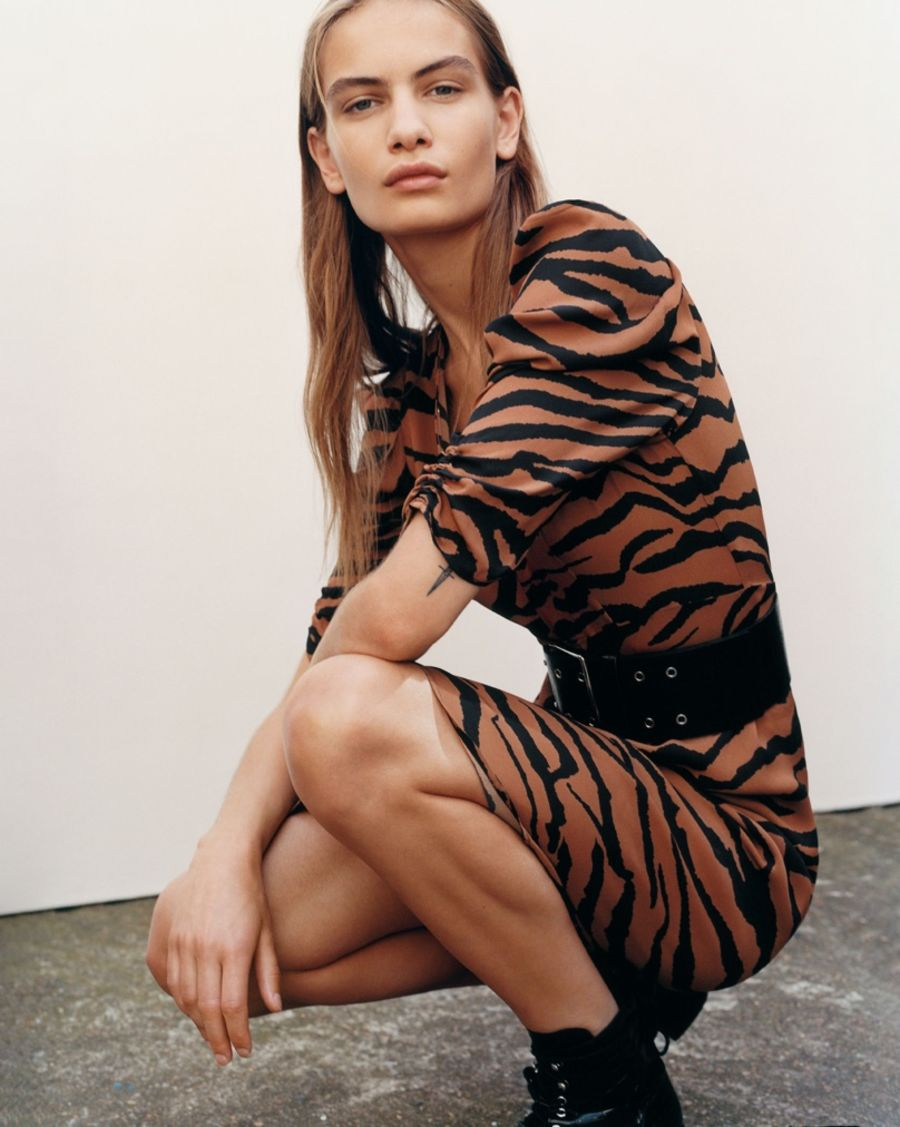 Image of a woman wearing a short brown zebra printed dress with a large black belt at the waist and black boots.