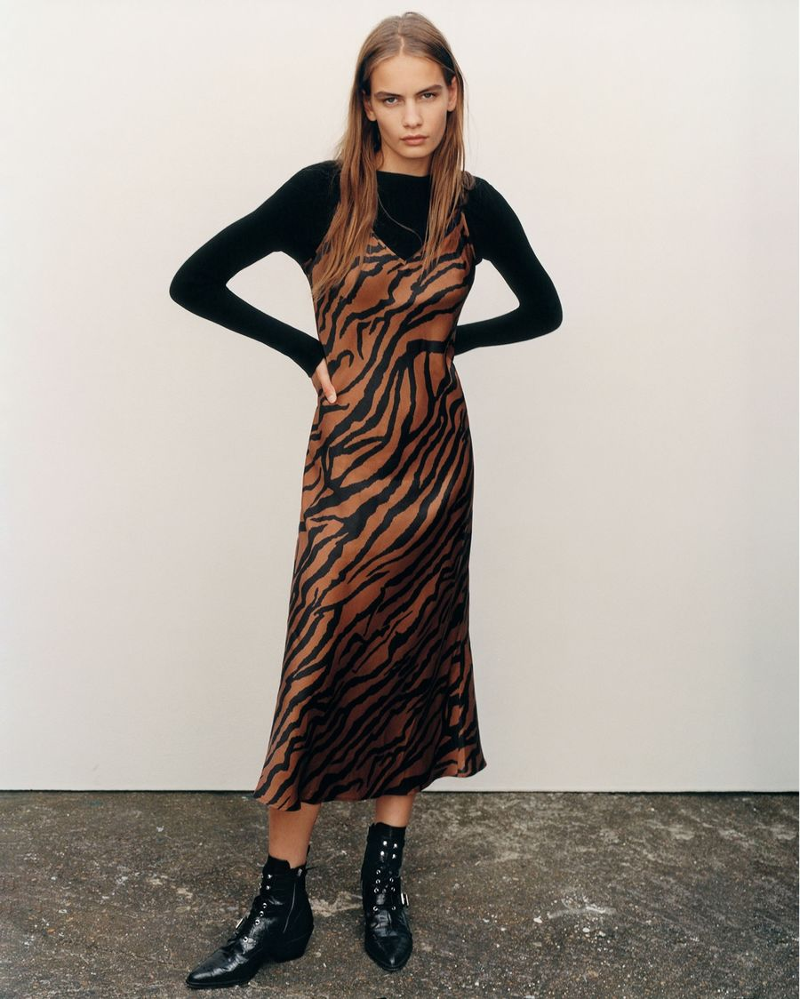 Image of a woman wearing a long zebra printed slip dress over a long sleeve black t-shirt with black leather boots.