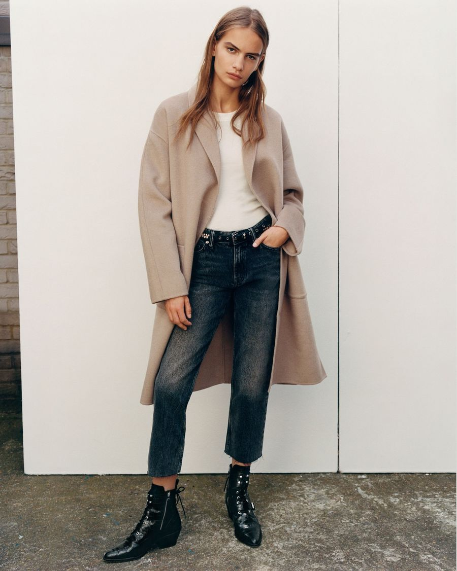 Image of a woman wearing dark blue denim jeans with a white t-shirt, camel coloured coat and black leather boots.