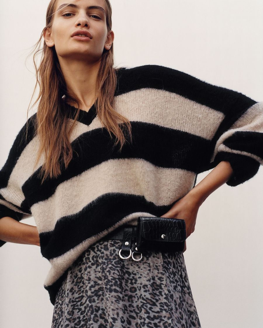 Cropped image of a woman wearing a striped jumper with leopard printed skirt.