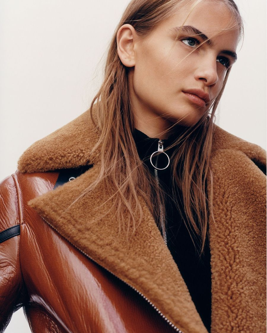 Close up of a woman wearing a brown shearling jacket.