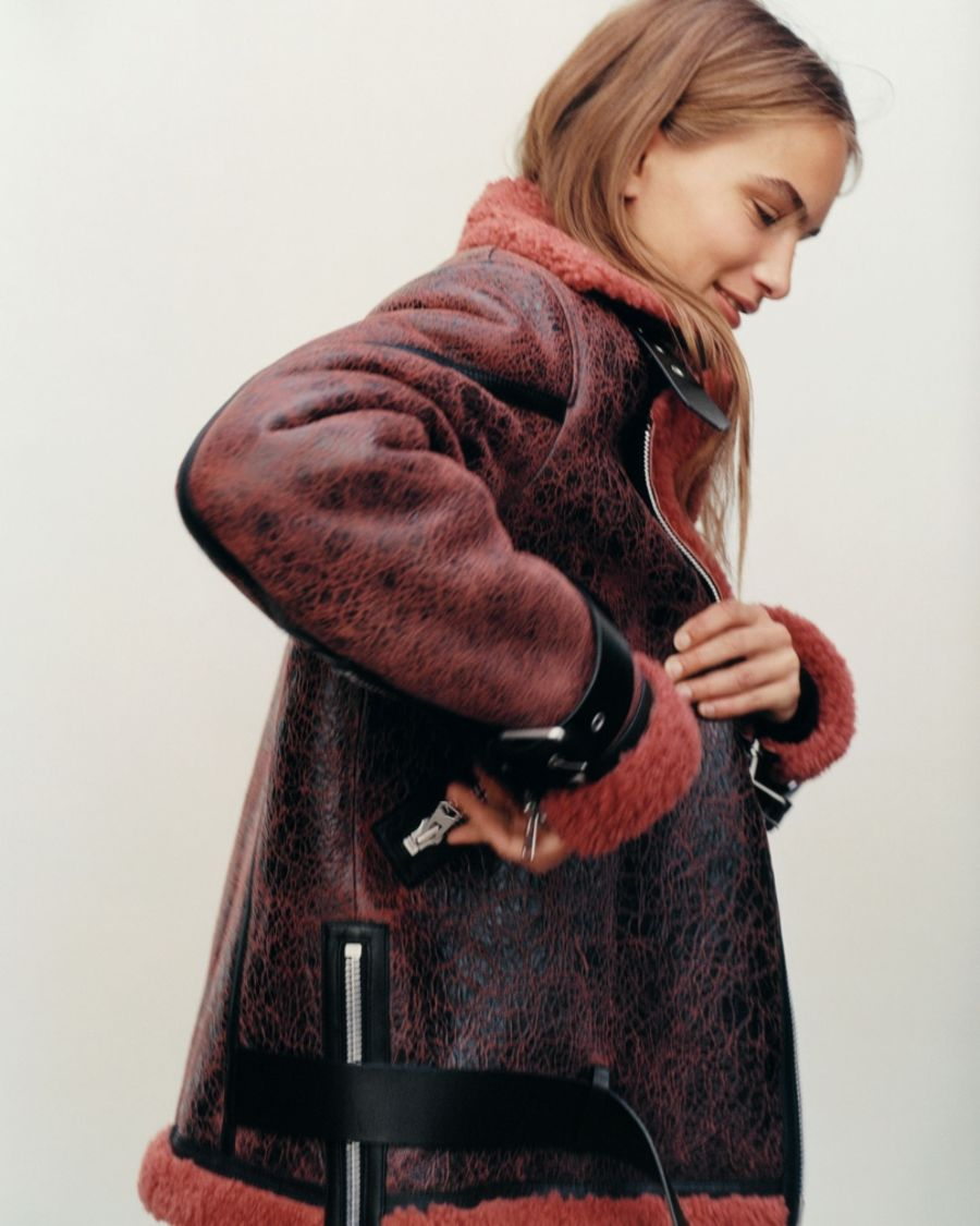 Profile portrait of a woman wearing a rusty coloured shearling jacket.