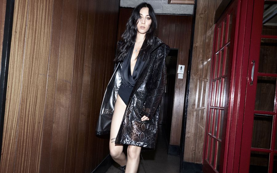 Image of a woman walking in a corridor wearing a black bodysuit with a snake printed patent coat and black boots.