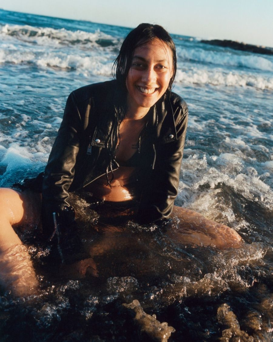 Woman sitting in the water on the beach wearing a black leather biker jacket over a black bikini.
