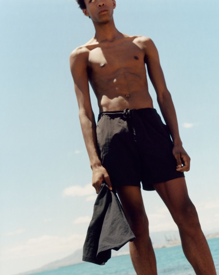 Cropped image of a man standing on a beach wearing black swimshorts and holding a black t-shirt.