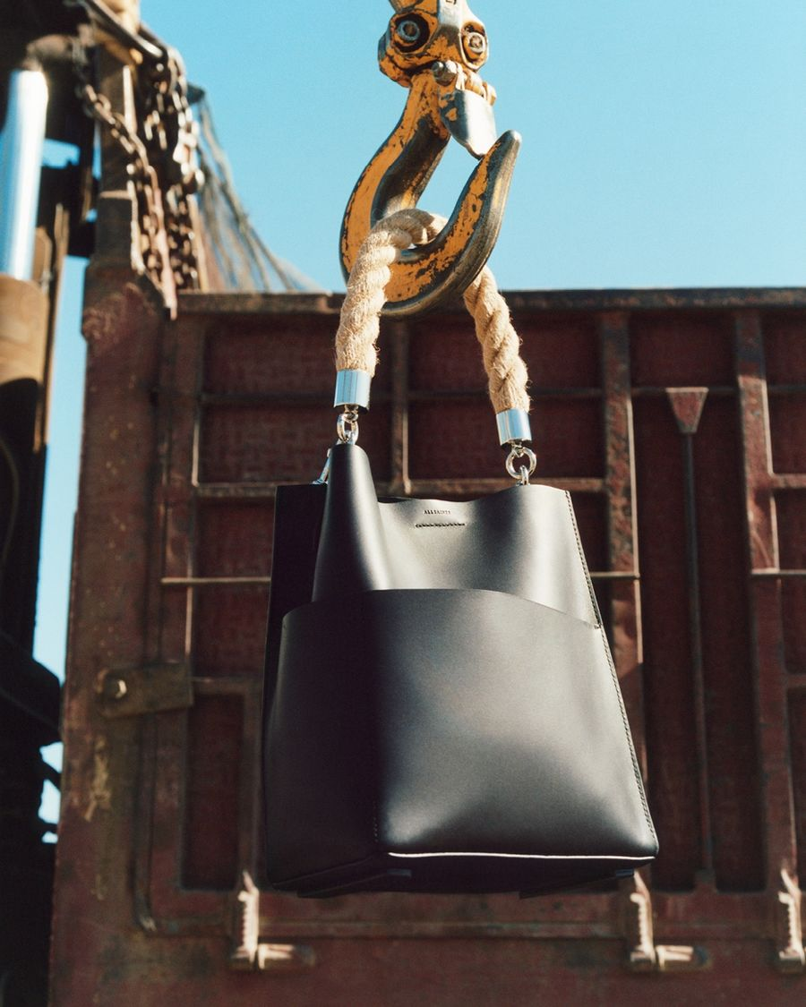 Picture of a black leather tote bag with rope handle hanging from the hook of a crane.