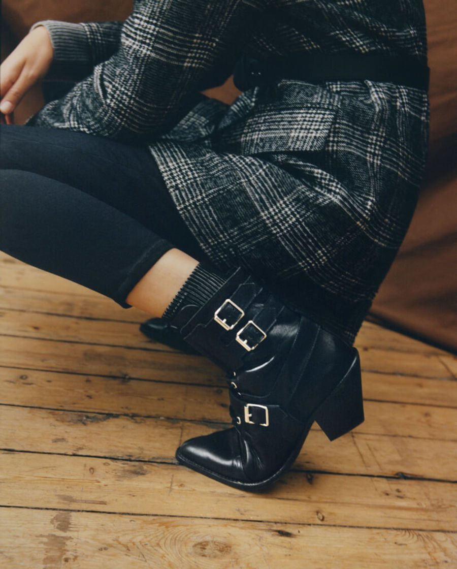 Close up on a woman wearing bblack leather boots with black jeans and a checked blazer with a black belt at the waist.