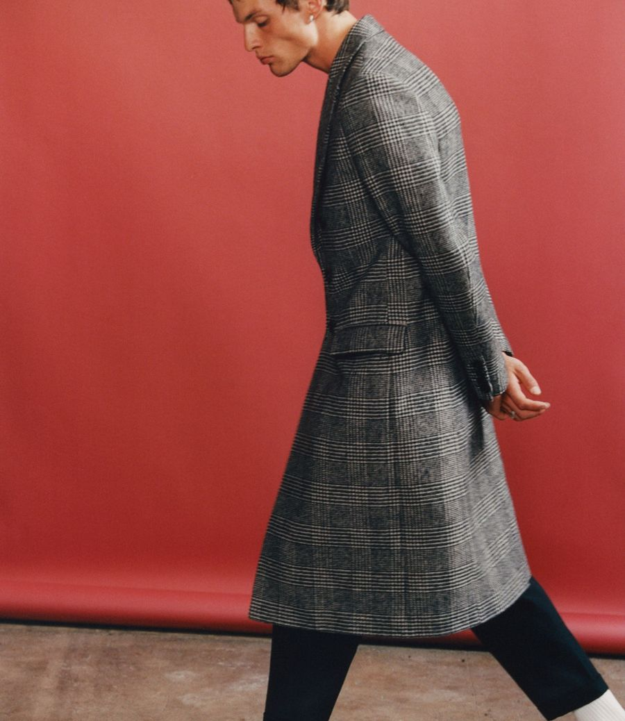 Image of a man walking in front of a red background wearing a long grey checked coat with black tailored trousers.