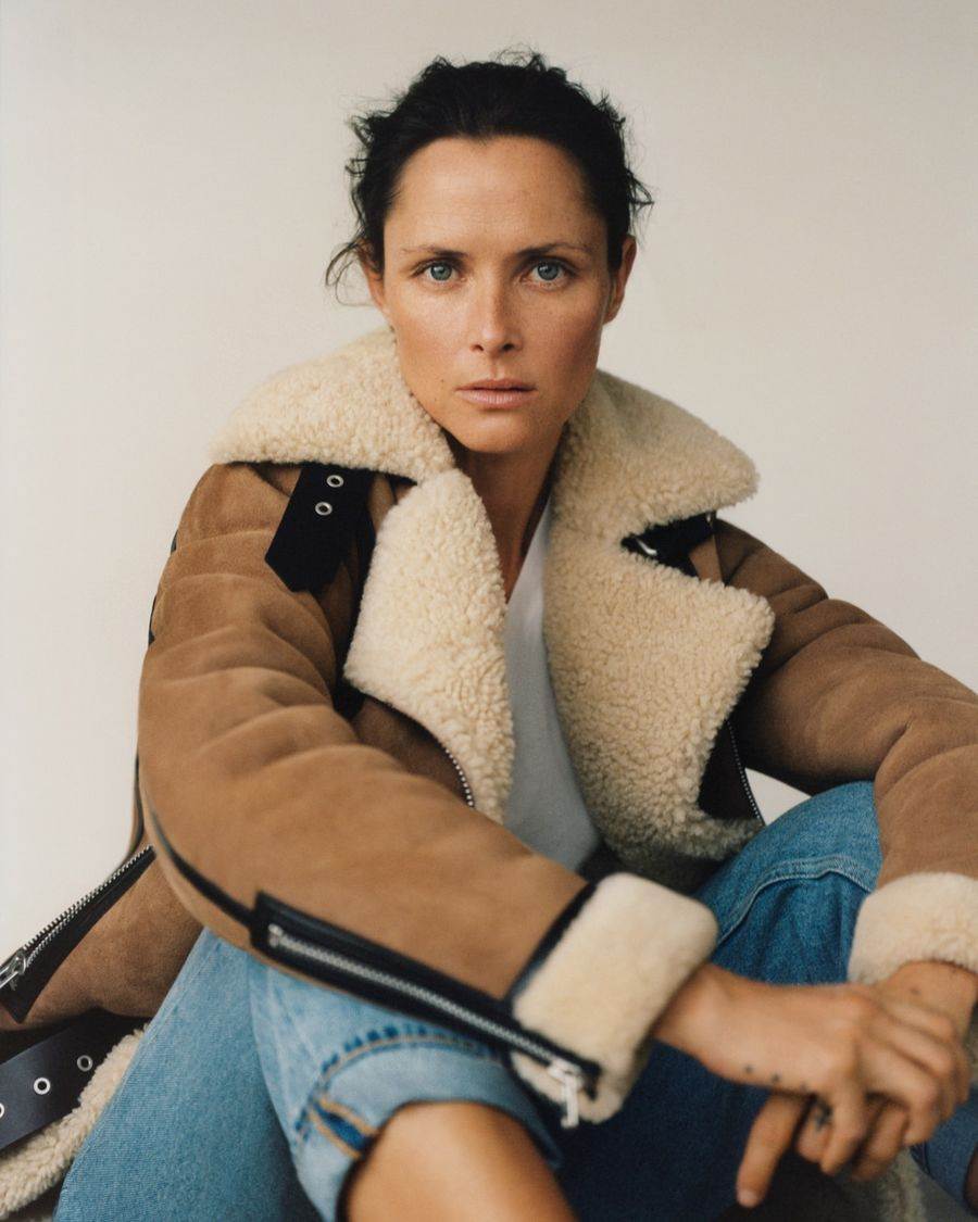 Image of a woman sitting on the floor wearing a tan shearling jacket over a wite t-shirt and light blue denim jeans.