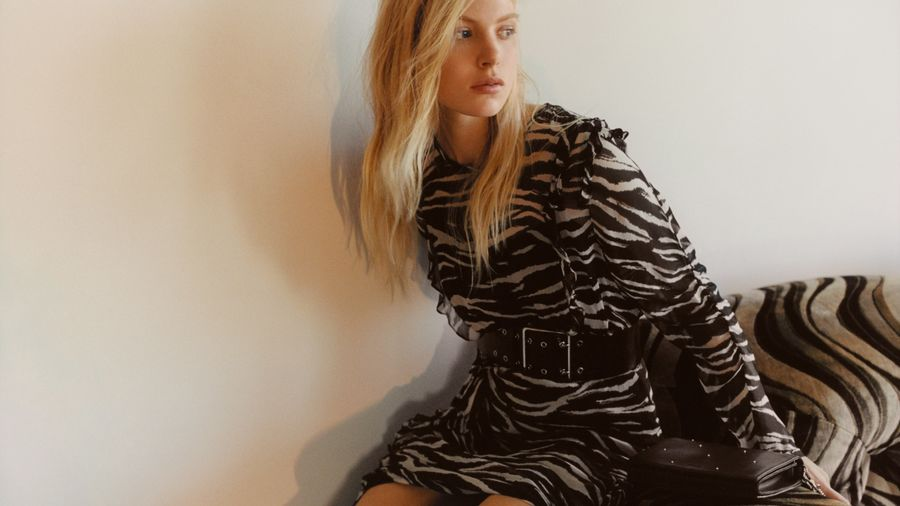 Image of a woman seating on a couch wearing a short zebra dress styled with a black leather belt at the waist.