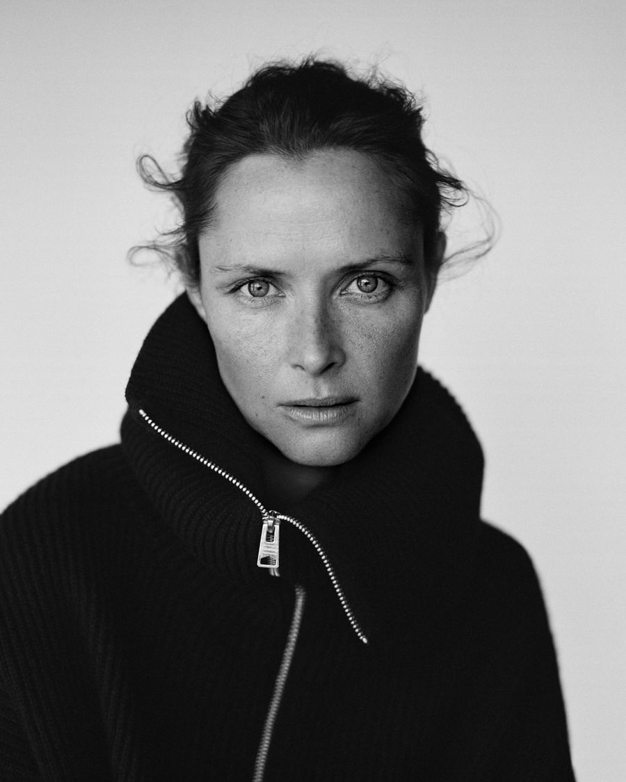 Black and white portrait of a woman wearing a zipped roll neck jumper.