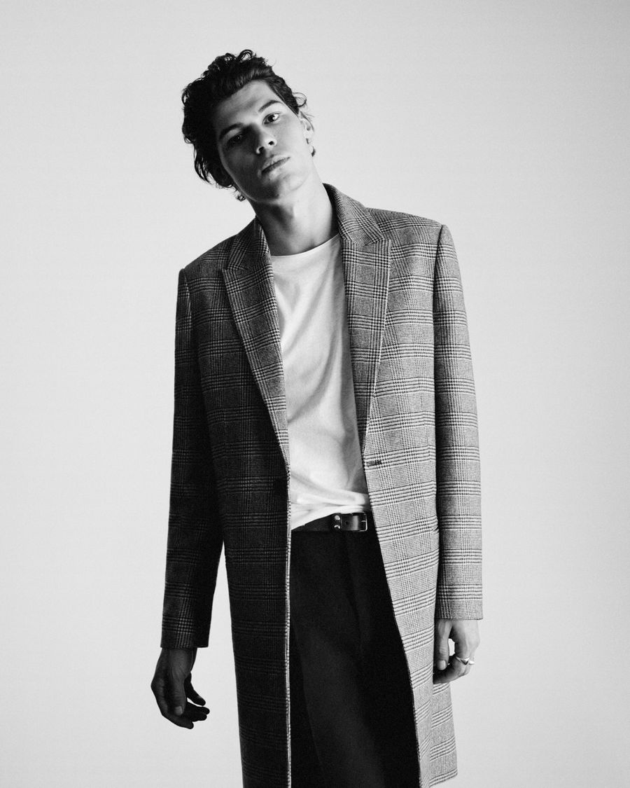 Black and white image of a man wearing a long checked coat over a white t-shirt and black tailored trousers.