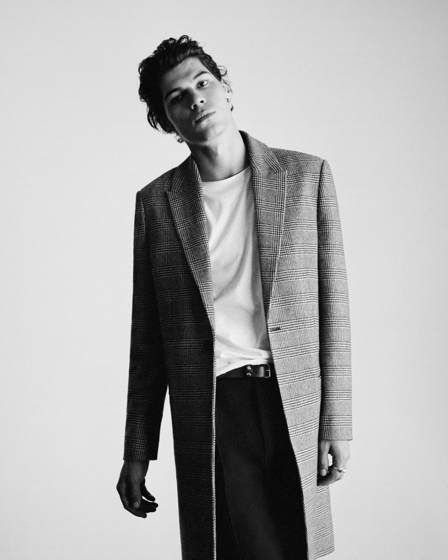 Black and white image of a man wearing a long checked coat over a white t-shirt and black tailored pants.