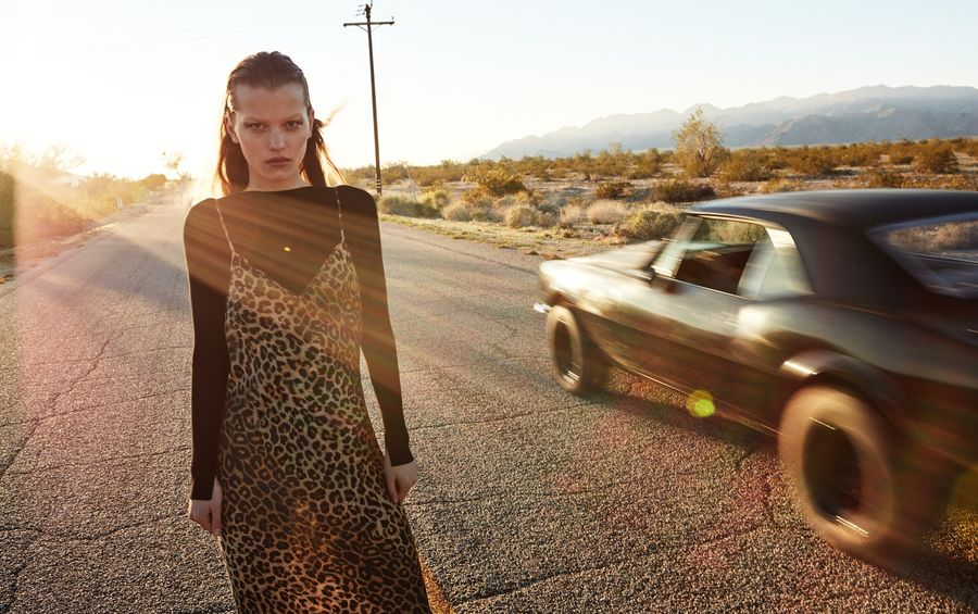 Image of a woman standing on the road near a black sport car and wearing a thin strap leopard print dress over a thin long sleeve jumper.