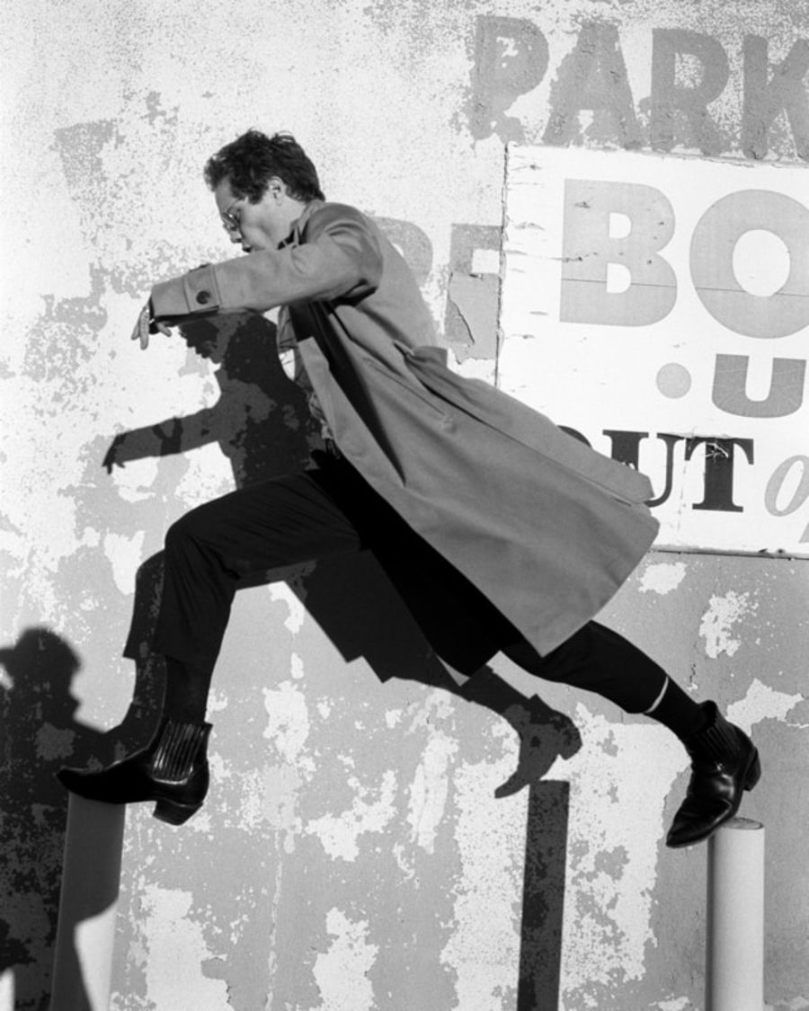Black and white image of a man jumping in the street wearing black tailored trousers, black western boots and a camel trench coat.