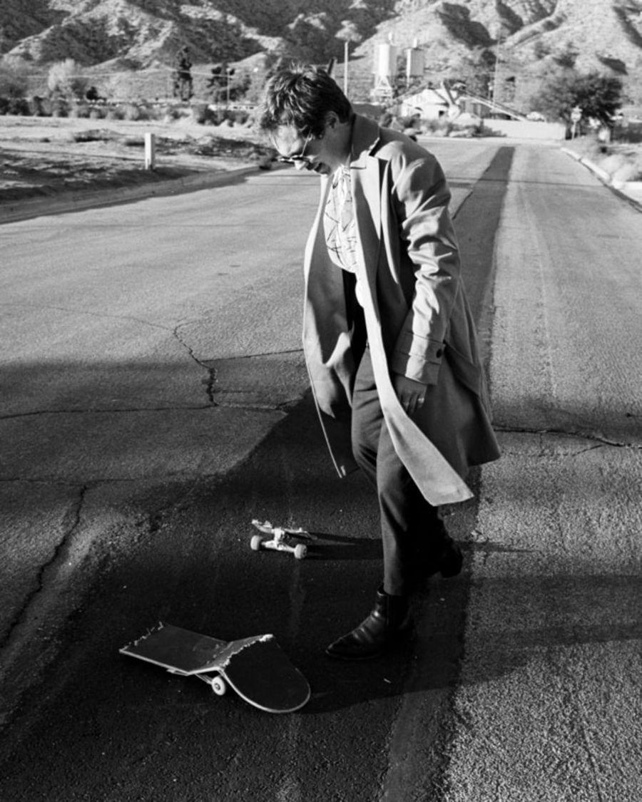 Schwarz-weißes Foto von einem Mann, der Kleidung aus unserer neuen Kollektion trägt und ein kaputtes Skateboard anschaut.
