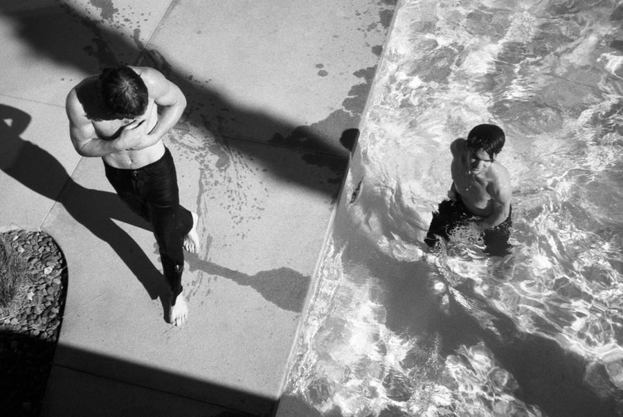 Black and white image of two men in a swimming pool wearing black tailored trousers.