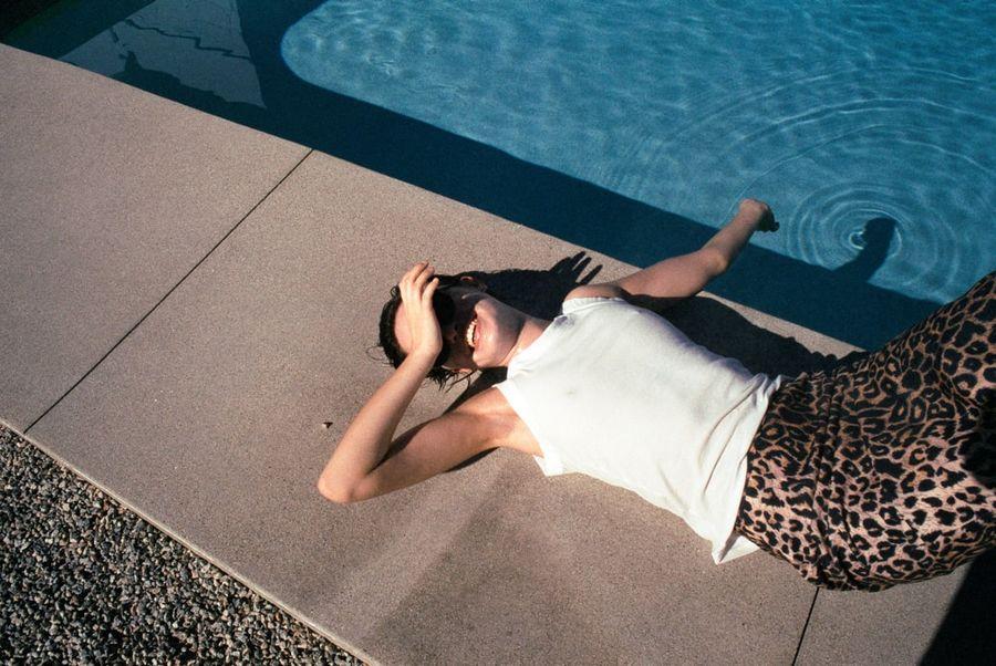 Foto von einer Frau, die neben einem Schwimmbecken liegt und einen Rock mit Leomuster und ein weißes Tanktop trägt.
