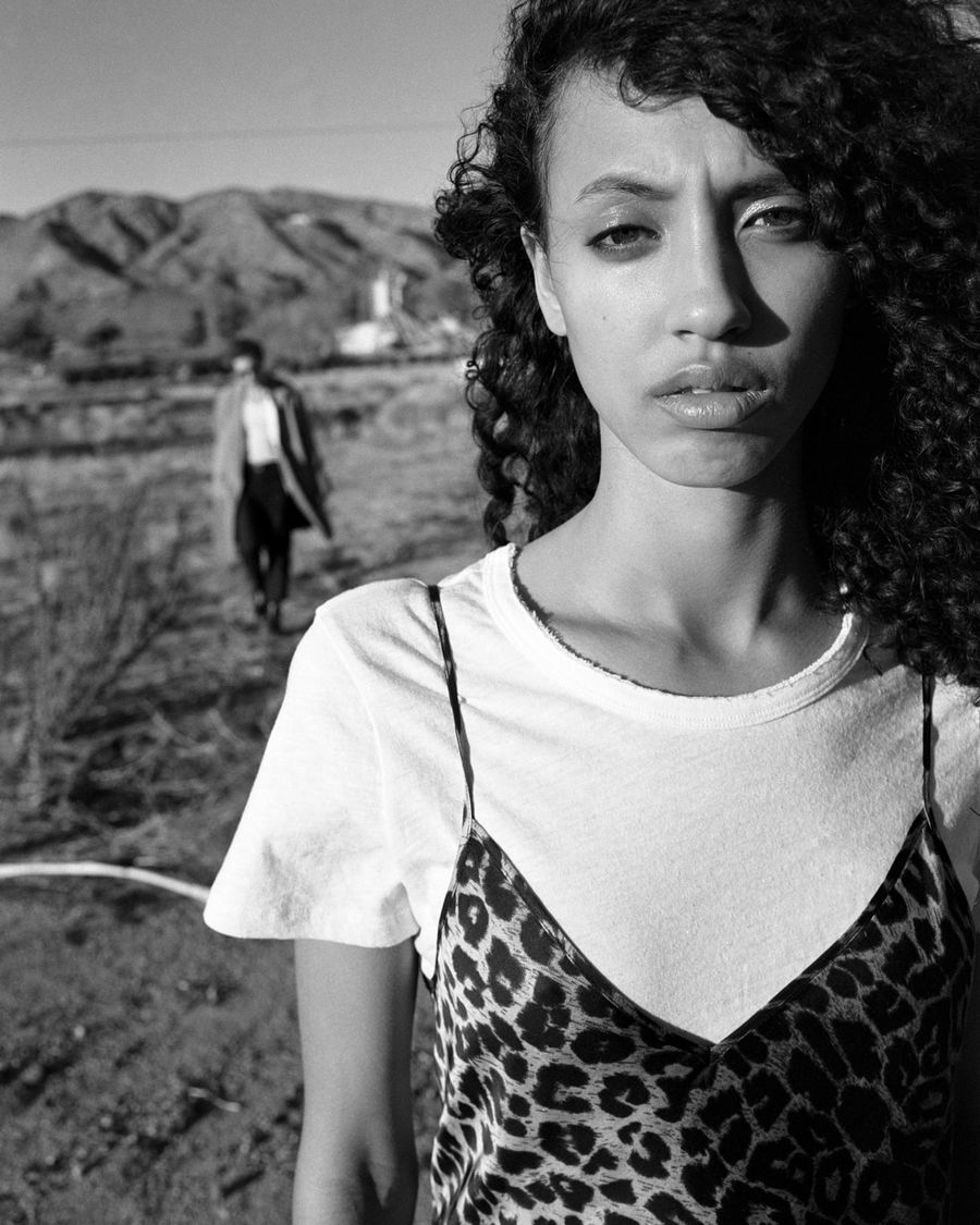 Black and white portrait of a woman wearing a thin strap leopard dress over a white short sleeve t-shirt.