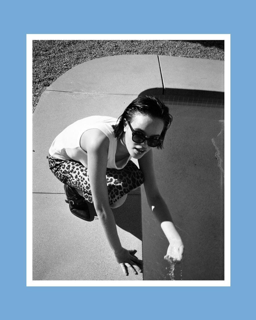 Black and white image of a woman crouched down near a pool and wearing a leopard skirt with white tank top.