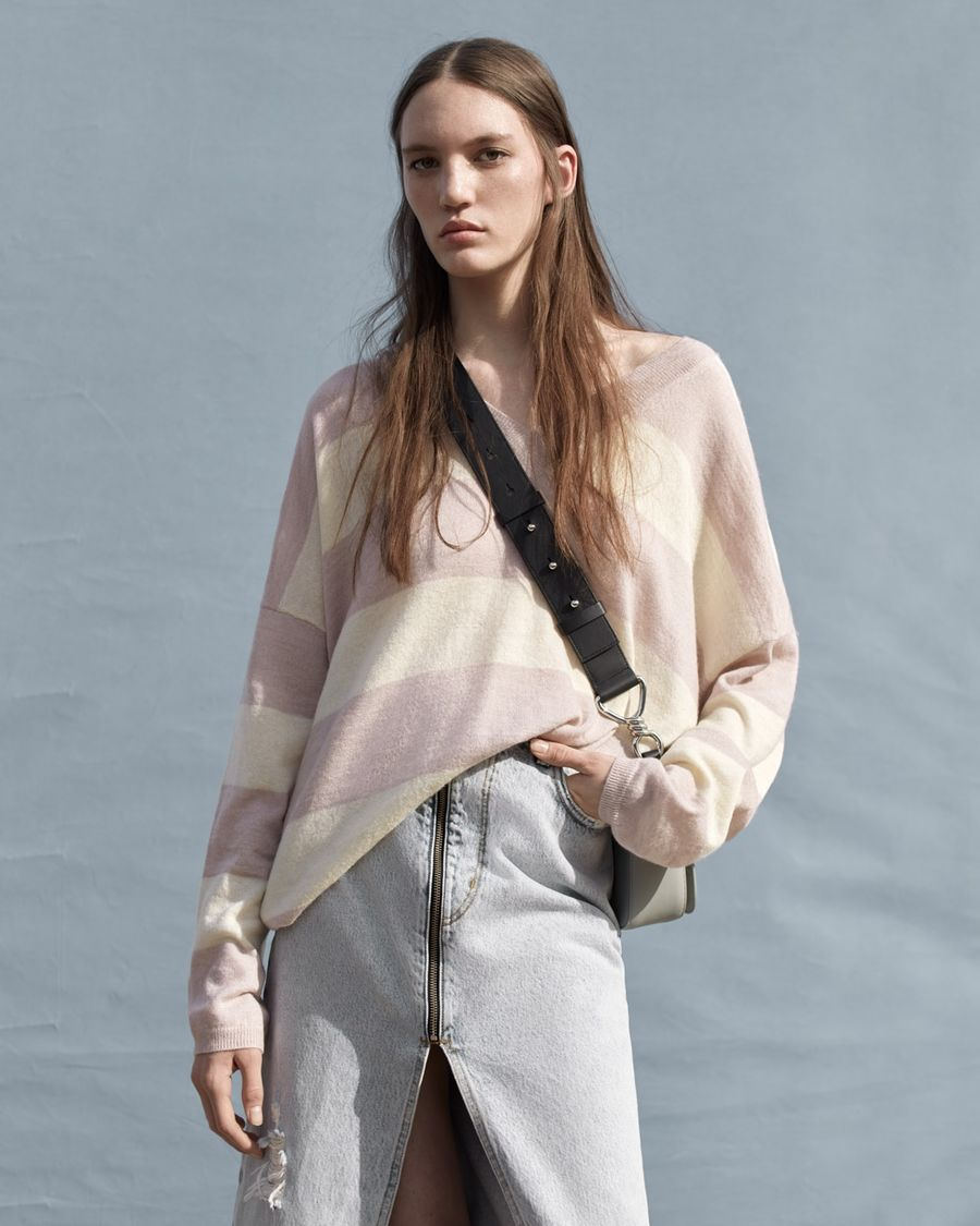 Woman wearing a light pink and beige striped v-neck jumper with a long zipped denim skirt and crossbody bag.